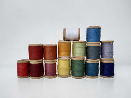 Colored spools of sewing thread on a white background. Sewing masks, clothes, multi-colored rainbow-colored threads. Small spools of colored thread stand in several rows, a wall of spools of thread on a white background in isolation