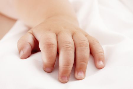 Baby hand lying on white sheet Stock Photo