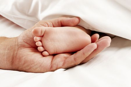 Dad holding baby feet Stock Photo