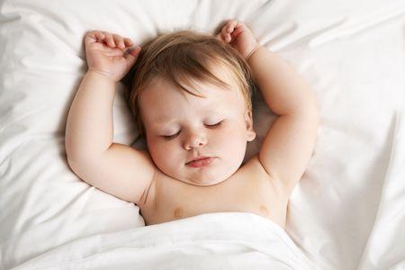 enfant qui dort: Dormir dans un lit de b�b�  Banque d'images