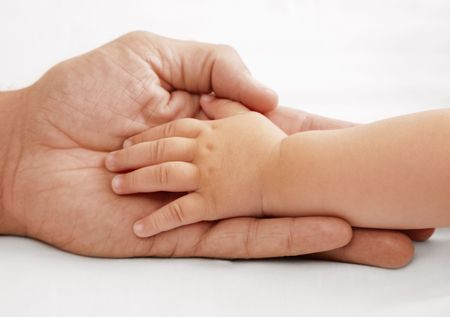 Baby hand lying in dads hand