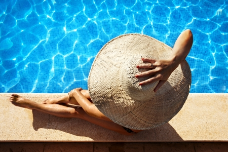 Woman with hat sitting at poolside photo