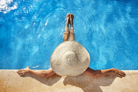 Woman with hat at poolside Stock Photo