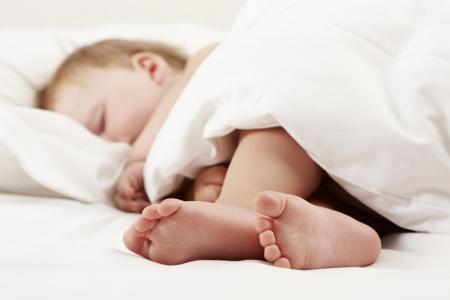 Baby sleeps on white sheet Stock Photo