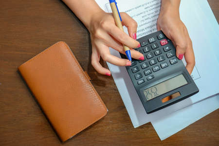A woman pressed a calculator to calculate income. Family expenses