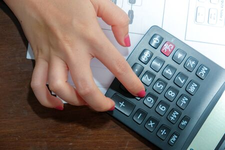 A close-up of a picture of a woman pressing a calculator,Business and finance concept.