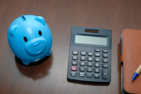 Piggy bank calculator with deposit put account on wood table.,Business and finance concept.