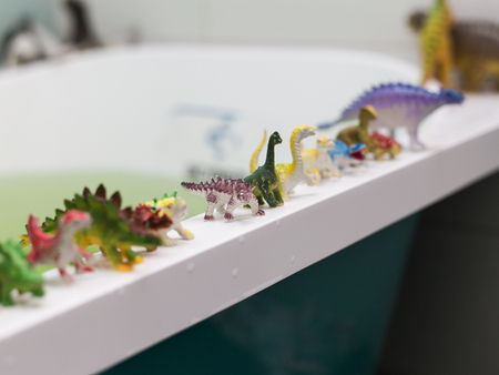 a lot of different toy dinosaurs at the bathroom.
