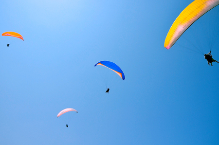 paroplane group flying against the blue sky.Above the Mediterranean Sea, Israel.Extreme sports, enjoy life, appreciate the time, tandem paragliding, controlled pilot
