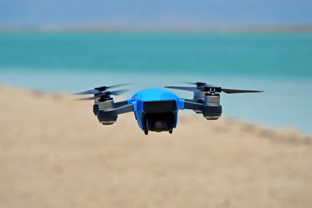 quadrocopter drone in rubber protection is hovering in the air against the background of the sea. a spark of new buzzing technology with a 15-minute flight time, with an intelligent sensor and brain.