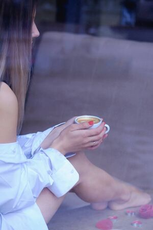 sexy girl sitting near the window and drinking coffee. single woman in white mens shirt, view from the back