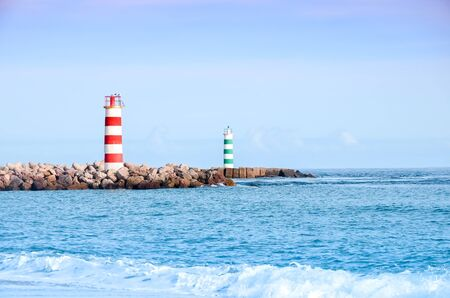 Two striped lighthouses stand on the beach in the city of Faro in Portugal. Little waves in the ocean on a sunny day