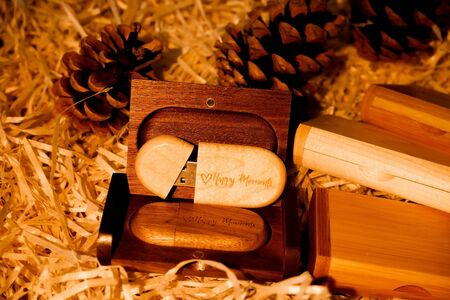Wooden brown usb flash drive with text Happy Moments with cones, brown warm background, data storage, beautiful photo feedback to client Reklamní fotografie