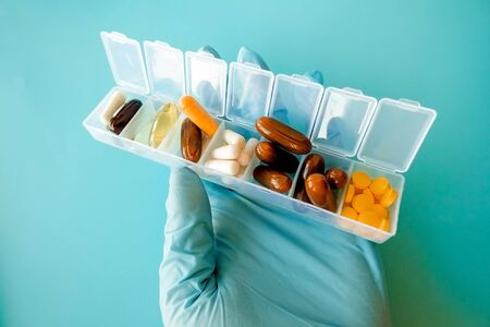 A hand with a medical glove holds multi-colored capsules, a pill box with medicines on a blue background
