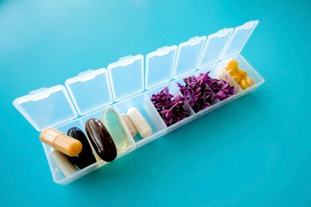 Capsules lie in a pill box on a blue background. Box for packing tablets for a week. Medicine and flowers, alternative medicine Stock Photo