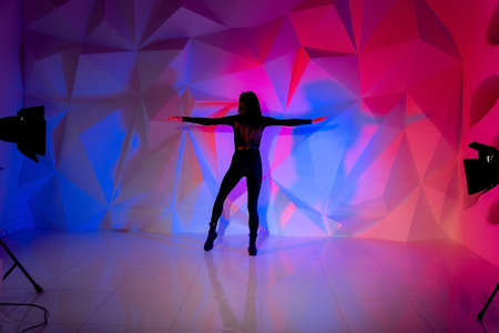 Woman dancing on the background of a beautiful multicolored wall. Sexy slim lonely girl with long black hair. female holds her head. bright colorful geometry background