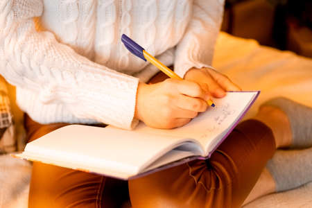 beautiful sexy girl sits on the bed with a notebook and dreams. details close up.