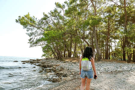slender brunette girl in denim shorts and a white tank top. woman tourist with a backpack walking along the lagoon beach, view from the back, phaselis old town