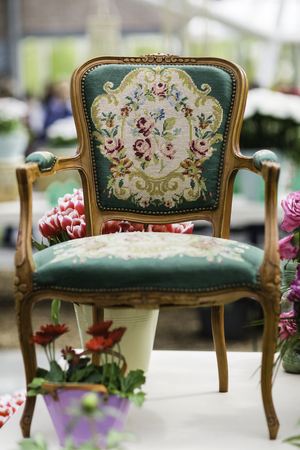 Wooden arm chair with beautiful fabric upholstery and flowers in the background Stock Photo