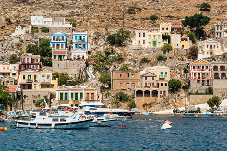 Seascape with panoramic view of the traditional colorful houses and the port called Yalos with the sailing boats in Symi island Dodecanese, Greece. Stock Photo