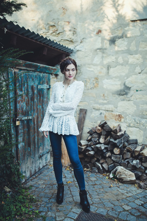 Beautiful brunette with braids around head in a stylish vintage white lace long sleeve blouse and jeans near the rural shed