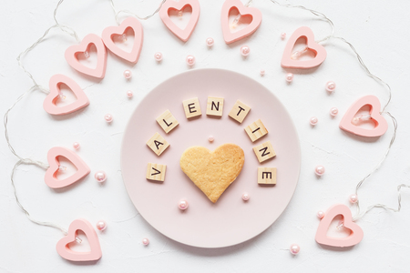 VALENTINE word and heart shaped butter cookie on a pink plate and Valentines Day decoration - heart shaped lights on a white background