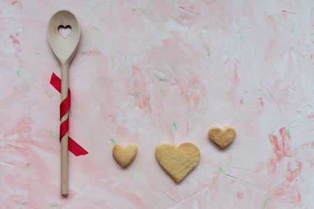 Stirring spoon and three heart shaped butter cookies on a pink background . Spring holidays cooking and celebration concept. Top view, flat lay, copy space.