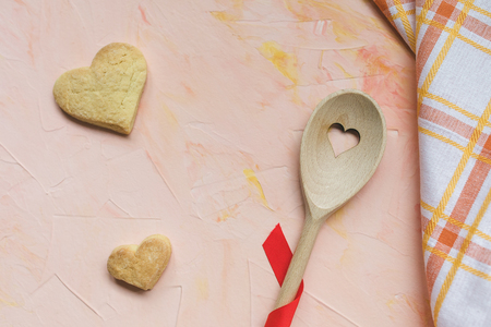 Stirring spoon, two heart shaped butter cookies and a kitchen towel on a pink background . Spring holidays cooking and celebration concept. Top view, flat lay, copy space.