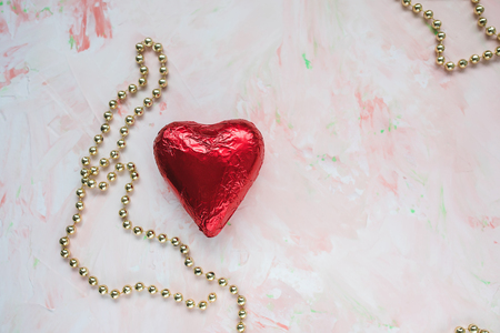 Chocolate heart in red foil and golden decorative beads on a pink background. Valentines Day concept, copyspase.