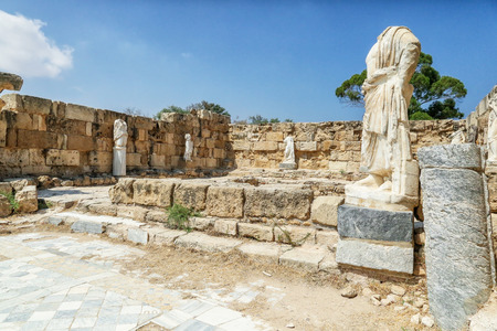 Famagusta, Turkish Republic of Northern Cyprus. Corinthian columns and sculptures at bath complex in ancient city Salamis ruins. Sunny day, blue sky.