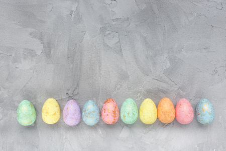 Pastel and gold colored eggs decoration on a gray background. Easter celebration concept. Top view, flat lay, copy space.