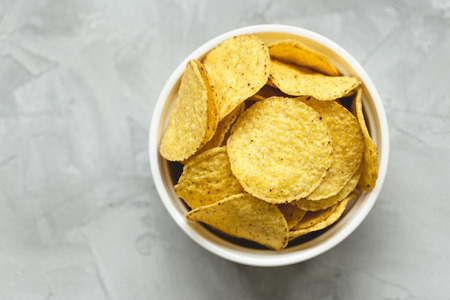 Tortilla nachos corn chips in a porcelain bowl on a gray background. Traditional Mexican meal. Close up, selective focus, copy space.