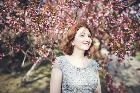 Happy middle aged Armenian woman in an elegant dress under the blooming sakura tree. Smiling and squinting.