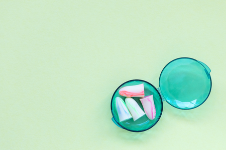 Two pairs of earplugs in a box on the green background. Good sleep and noise protection concept. Copy space.