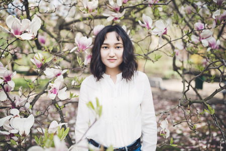 Happy asian young woman in a white blouse under the blooming magnolia tree. Smiling, looking at the camera.