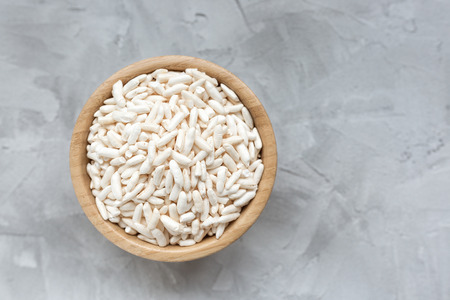 Puffed rice in a wooden bowl on a gray background, concept of healthy eating vegan food. Close up, selective focus, copy space.