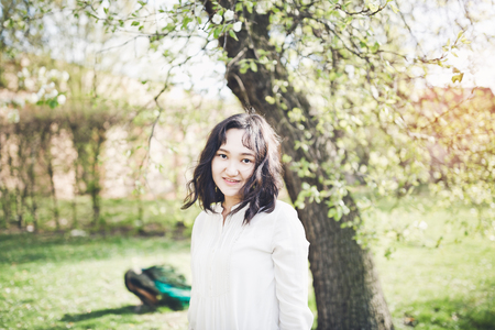 Happy asian young woman in a white blouse and jeans in the garden, peacock in the background. Springtime.