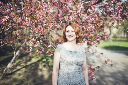 Happy middle aged Armenian woman in an elegant dress under the blooming sakura tree. Smiling, looking aside. Stock Photo