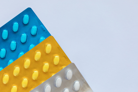 Set of various tablets in a blue, yellow and white pack blister pack. Healthcare and medical concept. Copy space, white background.