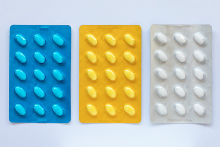Set of various tablets in a blue, yellow and white pack blister pack. Healthcare and medical concept. Close up, white background.