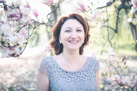 Happy middle aged Armenian woman in an elegant dress under the blooming magnolia tree. Smiling, looking at the camera. Toned, selective focus. 写真素材