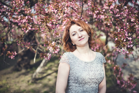Happy middle aged Armenian woman in an elegant dress under the blooming sakura tree. Smiling and squinting in the sun. 写真素材