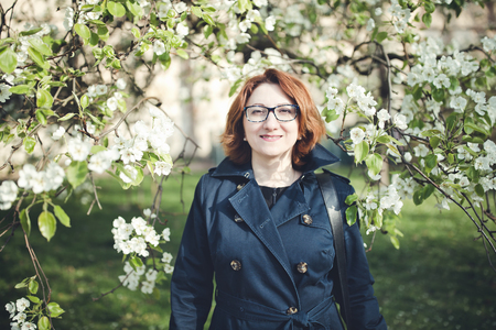 Confident middle aged Armenian woman in a blue trench coat and glasses under the blooming tree. Smiling, looking at the camera.