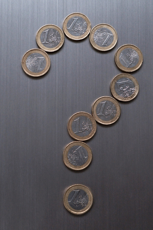 Question mark made of one euro coins on a metallic background. European currency finance concept. Close-up 写真素材