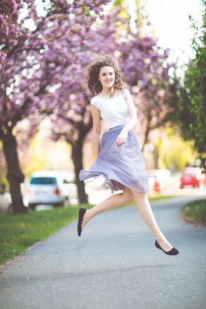 Young girl with curly hair in a white t-shirt and violet skirt dancing and jumping under the blooming sakura trees. Spring time.