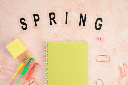 SPRING word and student desk workspace with notebook and pens on a pink backround. Flat lay, top view, social media hero header template.
