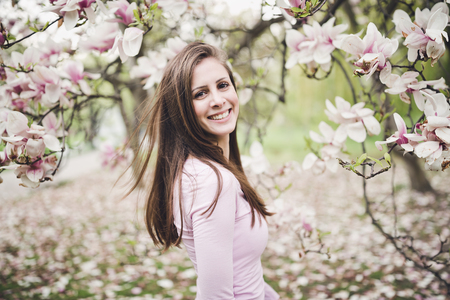 Happy long hair young woman in a pink shirt under the blooming magnolia. Smiling, looking at the camera.