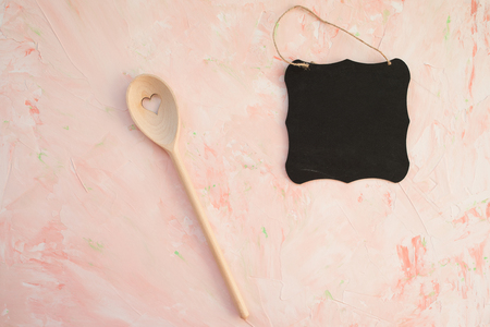 Empty blackboard and stirring spoon on a pink background . Cooking, menu and groceries concept. Top view, flat lay, mockup, copy space.