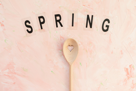 SPRING word and stirring spoon on a pink background . Spring holidays cooking and celebration concept. Top view, flat lay, copy space. 写真素材