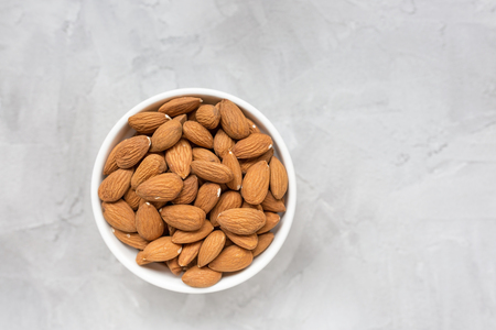 Raw almonds in a porcelain bowl on a gray background, concept of healthy eating vegan food. Close up, selective focus, copy space.